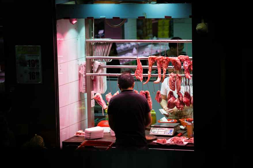 man standing in front of stall with hanged meats