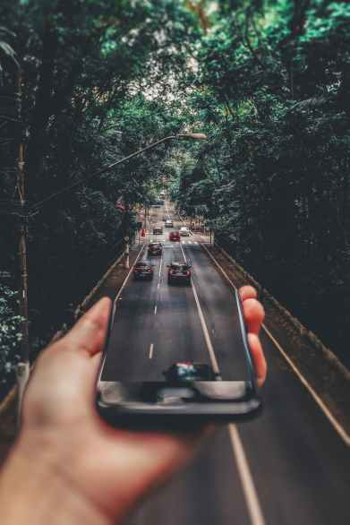 forced perspective photography of cars running on road below smartphone